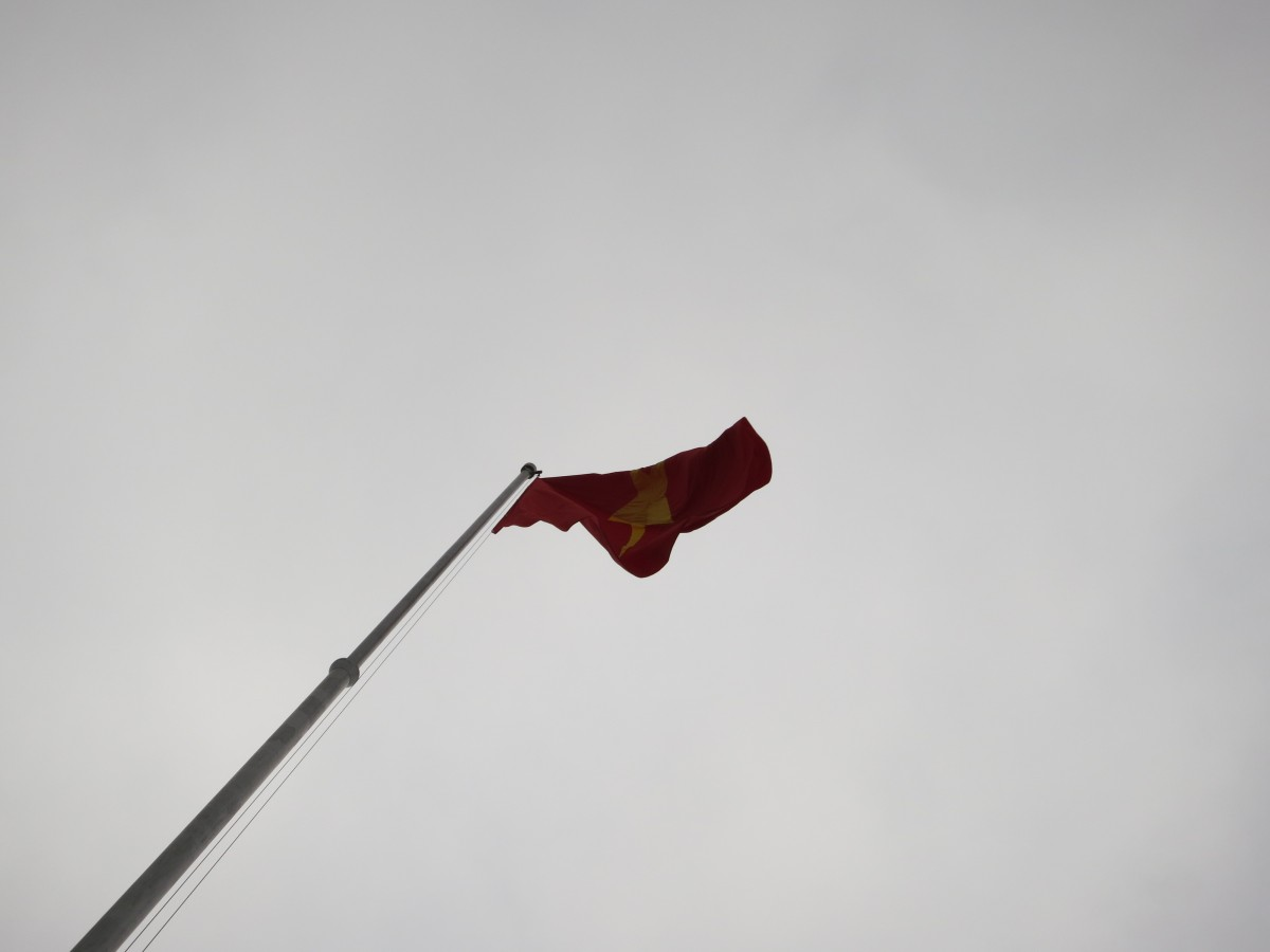 Vietnamese flag flying in front of the Ho Chi Minh Mausoleum