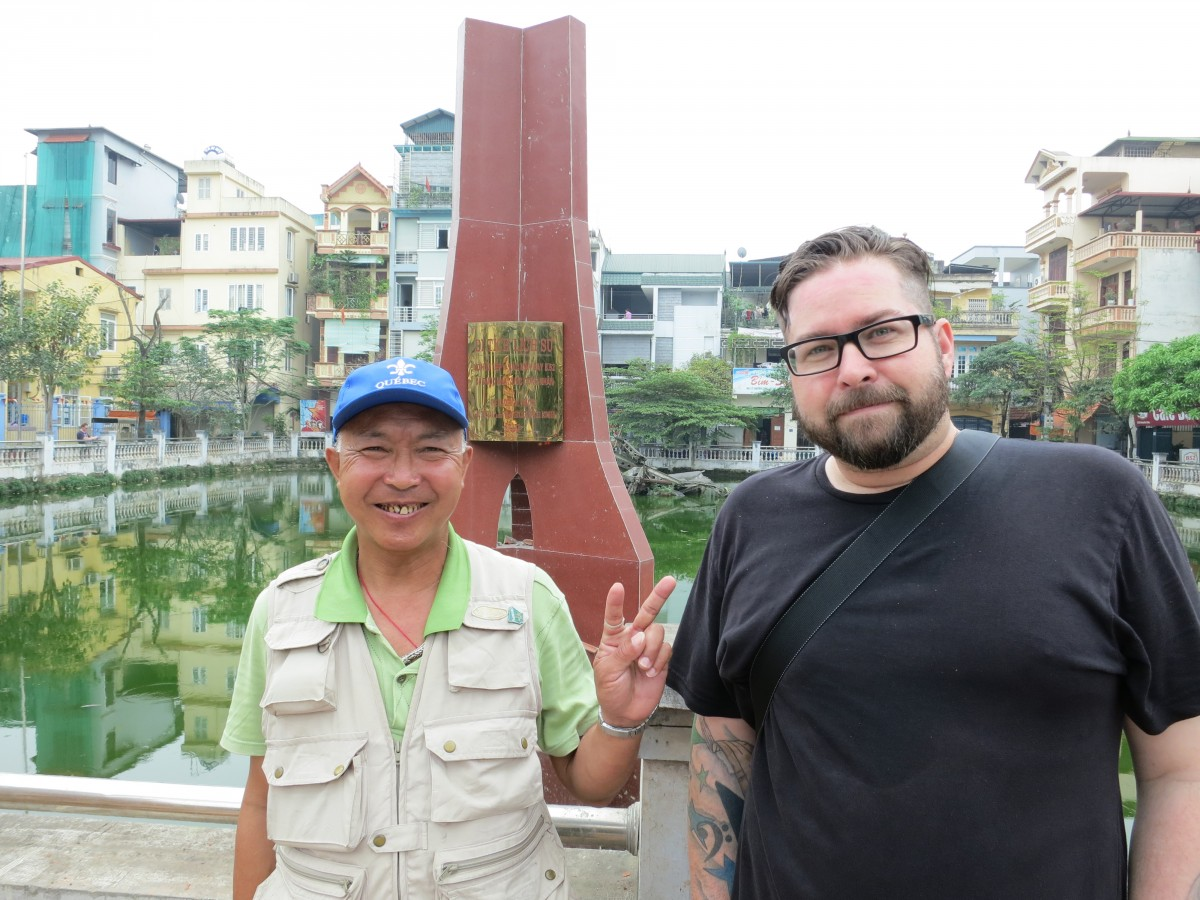 Duon and John in front of Huu Tiep Lake. Notice the wreckage of the downed B52 in the background. Duon was too young to serve in the American War, but remembers the bombings well.