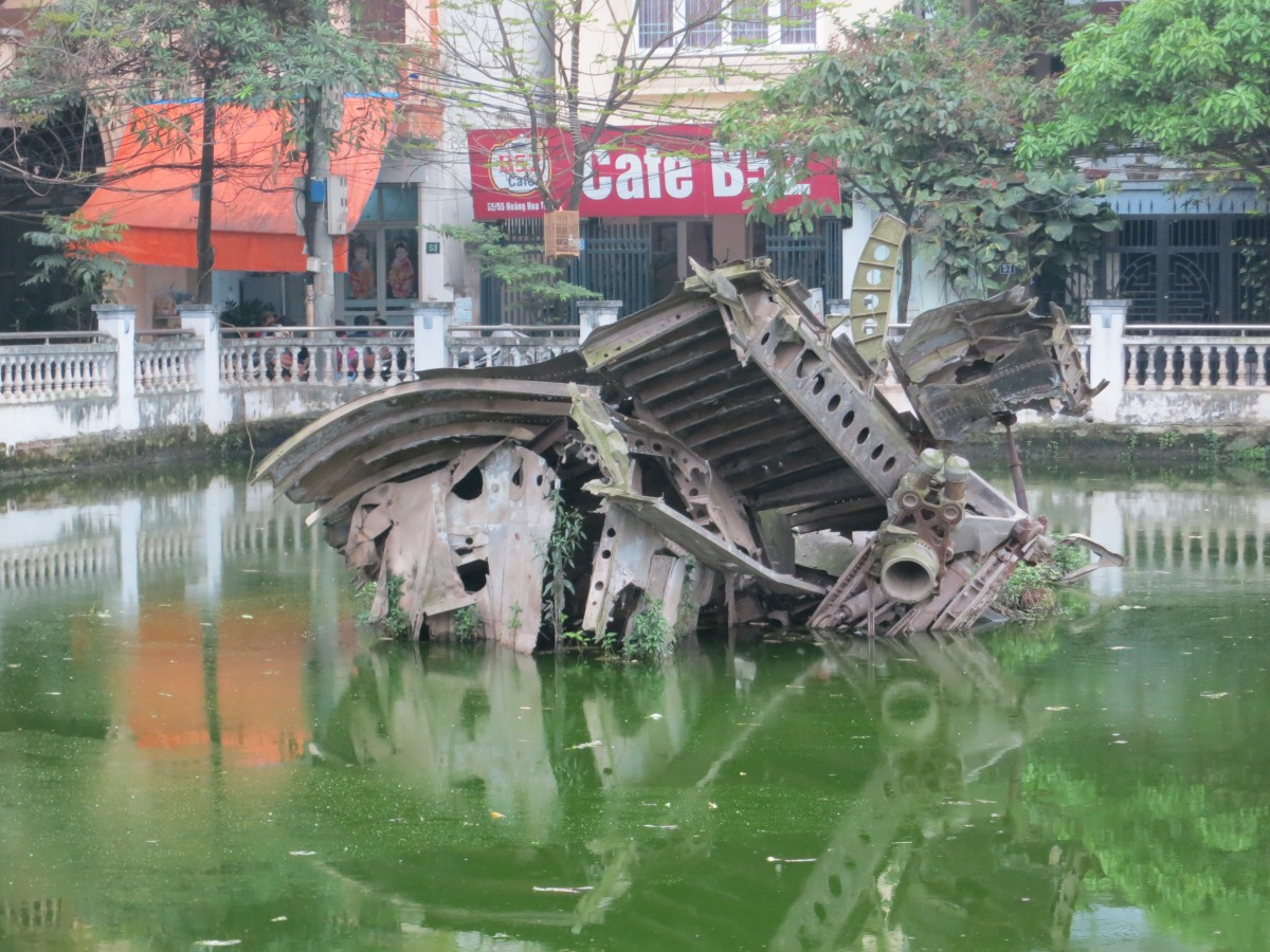 "Wreckage still sitting in a small lake in the middle of Ha Noi, from a downed B52 during what is called ""Dien Bien Phu in the Air"". Notice the cafe on the other side of the lake called Cafe B52."