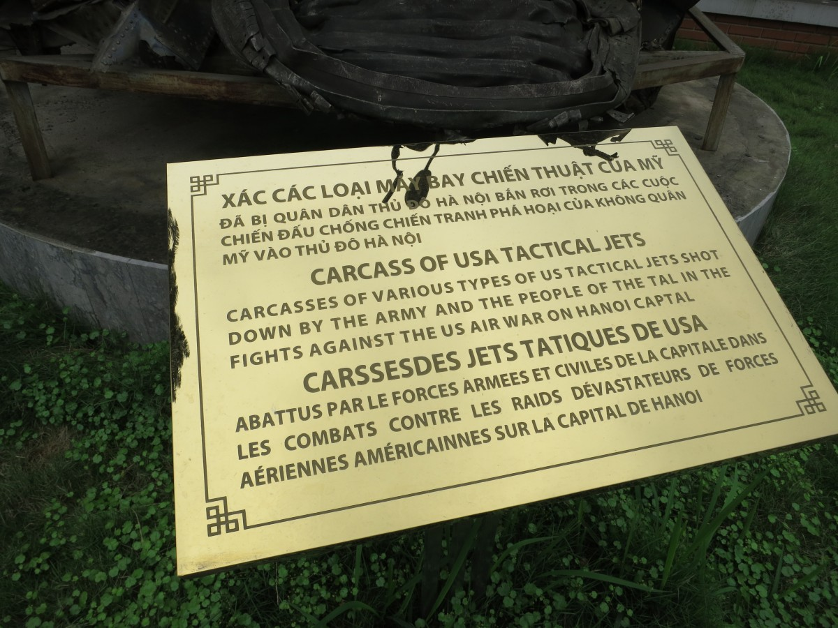 Plaque in front of a mess of metal from US aircraft that were shot down.